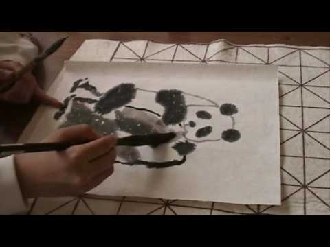 Amy drawing a panda bear with Chinese painting brush on a piece of rice paper with silver flakes