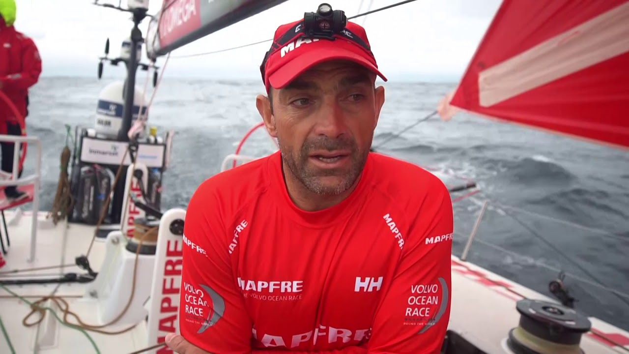 Xabi, in the cockpit talks in Spanish. Wind is about 12 knots. Talks about Turn the Tide and AkzoNobel, the approach to Newport. Repeats in Spanish: The last 24 hours we knew would be very tricky. Last night had winds up to 35 knots downwind. Now we've passed the front and we're going upwind with 7 or 8 knots. Going to be a compression. Managed to pass Turn the Tide, and made some distance as well with AkzoNobel. Are now 8 miles from Vestas. Still some hope. A lot can happen. Crew stacks to leeward in anticipation of a tack. Working the jury-rigged keel turing the tack. Joan, Xabi, and Neti clustered over the nav station, talking in Spanish. Washing machine from the cabin looking aft. Rob on the helm; Xabi on the pedestal. As it gets dark, wind is lighter, Rob looks to starboard through binoculars. Willy forward for a sail change. Looks like going from MH0 to J0 or vice versa.