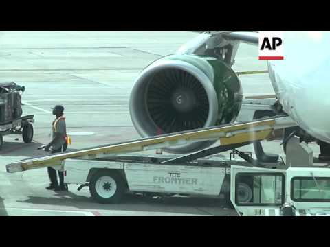 Passengers boarding a Frontier Airlines plane prepare to travel following reports that a second heal