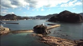 長﨑港入口に立つマリア観音 左側中腹に神の島教会が見えます。