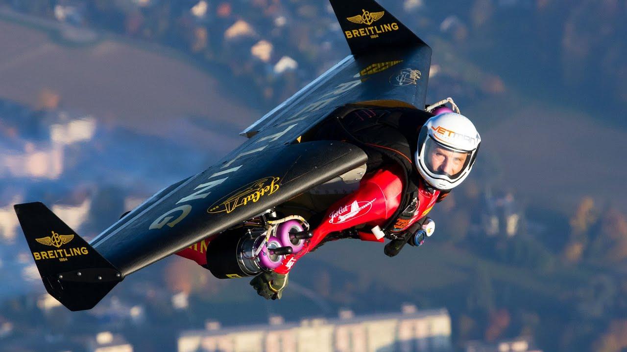 Yves Rossy fliegt mit dem Breitling Jetpack neben einem Flugzeug