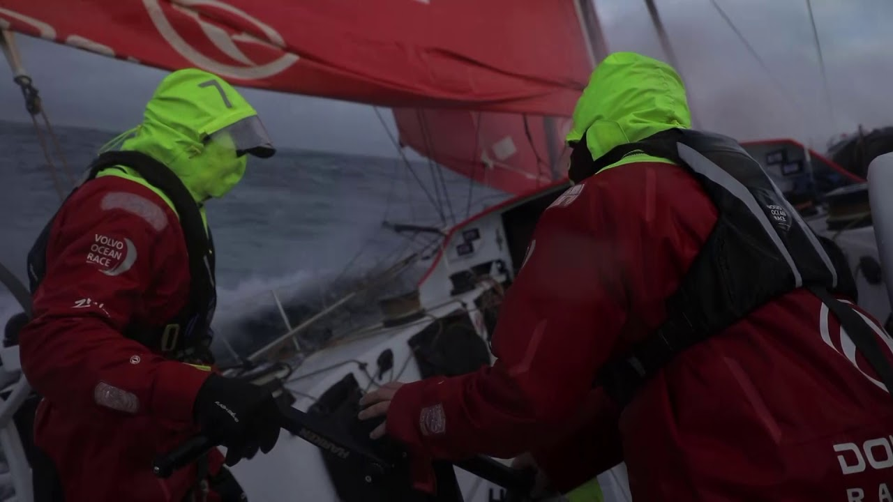 Dongfeng on port gybe, Carolijn trimming. MAPFRE to starboard. Daryl. Hoisting the J1. Charles grinding on the forward pedestal. Stu on the helm talking with Kevin. Spray. Sunset. Waves. Reefed main. Stacking. Pascal at the nav station. Charles at the nav station. Stu: If we had to gybe it though, we could run one. Stu: We've chosen a path inshore. So there's lots of tricky navigation. Sand banks, separation schemes, wind farms. It's going to be an interesting night.