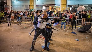 Police officer points gun at protesters in Hong Kong