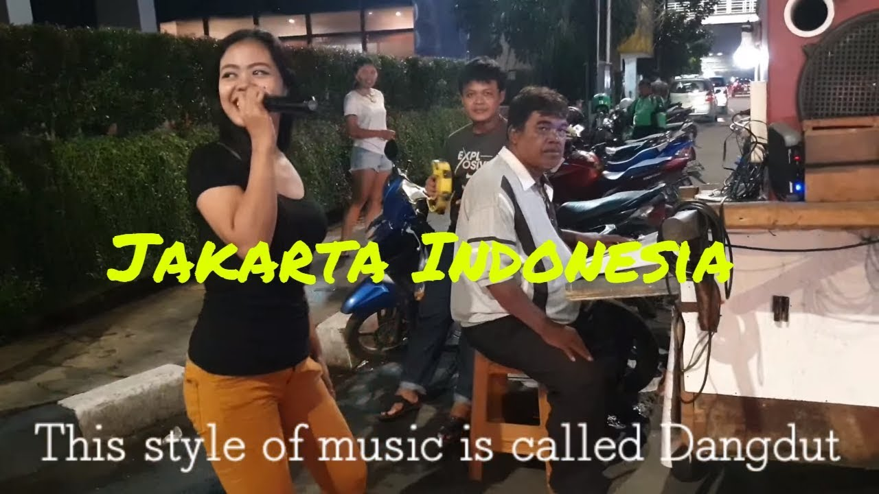 ? Local girl sings Dangdut music at 2am on the Jakarta streets of Indonesia