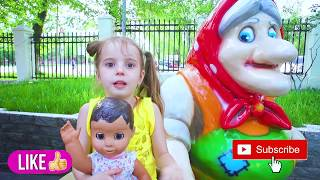 Арина и кукла играют в прятки в парке развлечений. Arina playing hide and seek with doll