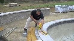 Laying pavers around pool coping