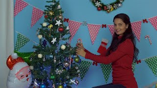 Happy Indian female hanging colorful balls on Christmas tree in casual clothing