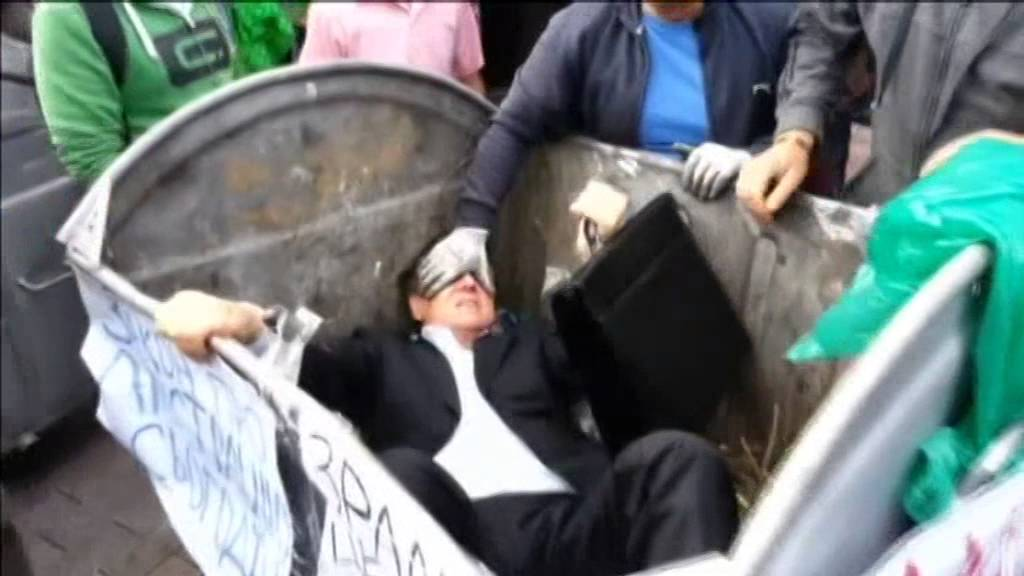 The politician tries to escape from the bin.