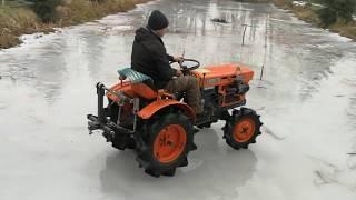 Kubota 7001 pod traktorkiem na stawie pęka lód .Dzikie drifty .