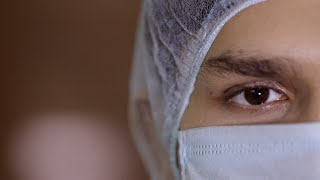 Extreme close up of a young medical professional wearing surgical mask and cap