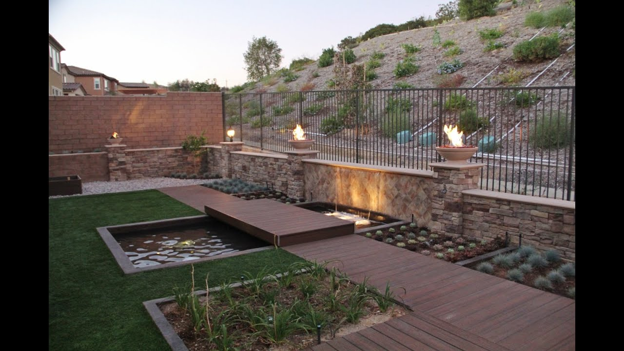 Modern backyard with a pond, water fall, fire bowls and ...
