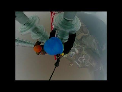 Cina, nebbia e vento non fermano gli operai: in bilico sui cavi a 380 metri di altezza