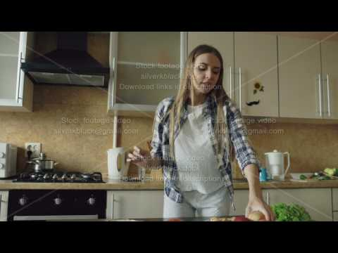 Cheerful young funny woman dancing and singing while cooking breakfast in the kitchen early morning