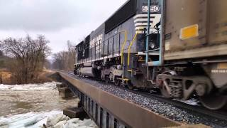 Ice jam just busted loose and train passes bridge.