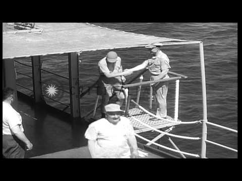 A sailor hands documents to a man working on a typewriter aboard USS Mount McKinl...HD Stock Footage