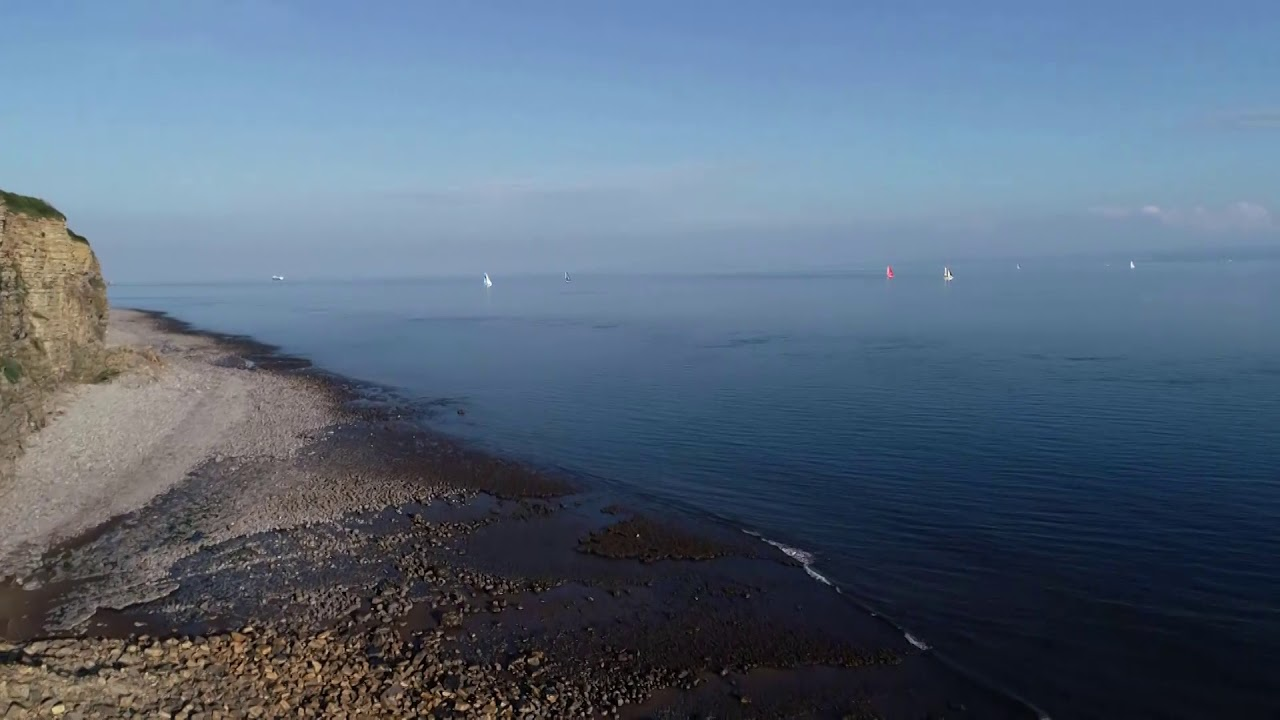 Drifting past coast. Carlo: Not actually a bad place, with the sun out. Nice little beach. Drone shots of people on shore, cliffs. Glassy conditions. Brunel with MAPFRE behind them. Low drone shot.