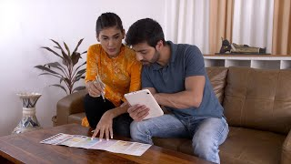 Young Indian couple using digital tab to pick the color of walls - Home interiors after home relocation