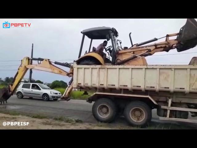 MOTORISTA DE PEDRAS DE FOGO RETIRANDO RETROESCAVADEIRA DE CIMA DE CAÇAMBA EM JACUMÃ