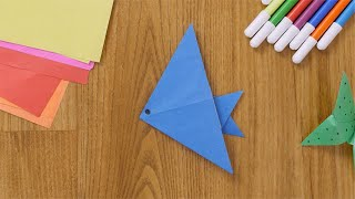 Overhead shot of girl's hand making an eye of a paper fish with a black sketch pen