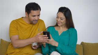 Newly married couple of India having fun while browsing social media on a mobile phone