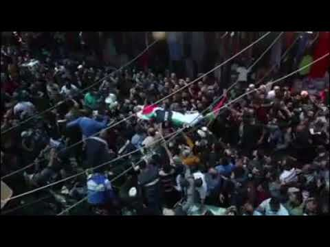Mourners and journalists carry the body of Palestinian journalist Yasser Murtaja