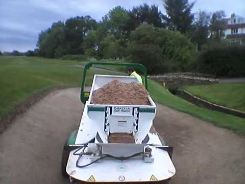 Greenkeepers Topping up bunkers with a Dakota top dresser