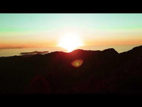 Coucher de soleil doré derrière mer serène et montagnes luxuriantes