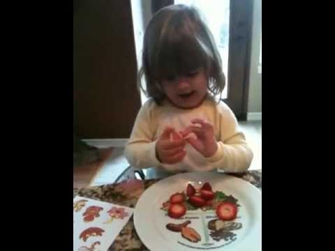 Little Girl Eating My Fruity Faces Edible Stickers On A Strawberry