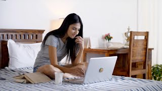 Beautiful Indian girl in bed using a laptop, drinking coffee and smiling - Technology