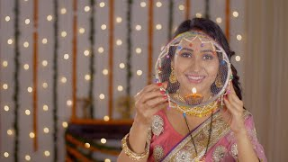 Pretty Indian woman happily looking into the camera through a sieve - Karwa Chauth concept