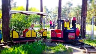 Цветные вагоны и детский паровозик в парке. Алина катается на детском поезде.