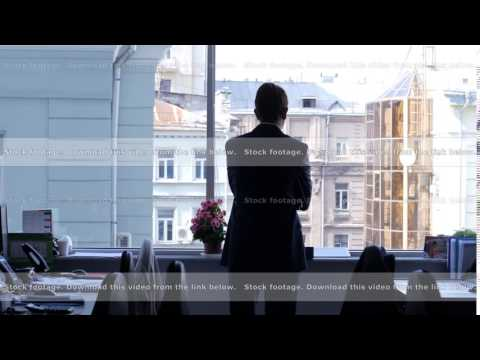Young businessman in suit walking between tables towards an office window while thinking over a