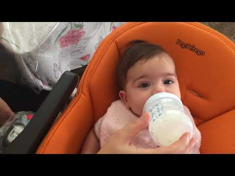 Liana baby girl using baby high chair drinking milk 4 months old