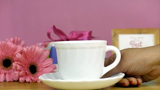 Woman hands placing a cup of tea/coffee on a decorated mother's day platform