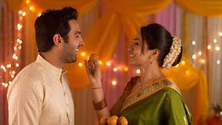Happy Indian nuclear family celebrating festival together - Young beautiful wife feeding laddoo to husband