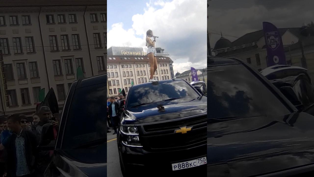 У машины девушка танцует парню