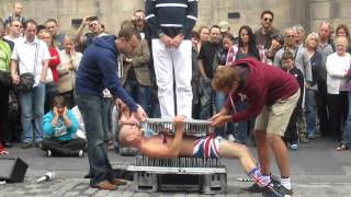 Mad guy sitting on bed of nails!!
