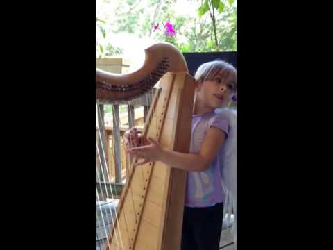 Child wearing wings plays Celtic harp