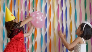 Cute little Indian girls playing with a pink balloon at a birthday party - Decorated wall for birthday party celebration