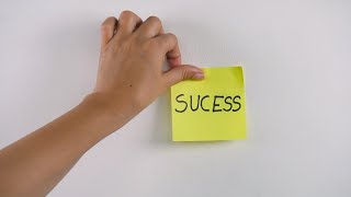 "Closeup shot of woman's hand sticking note with ""Success"" text on a white wall"
