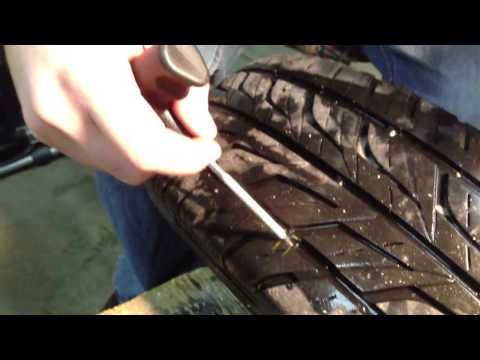 Fixing a flat tire by using a plug.