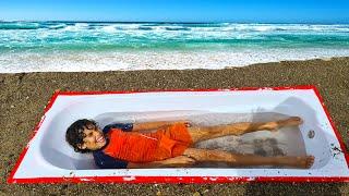 Bathtub buried in sand at the beach - ADEL ET SAMI