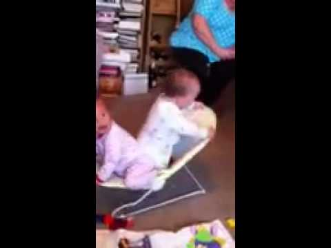 Two 1 year old twins bouncing on a baby chair