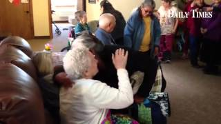 Cove Senior Center members hand out lap blankets to residents at BeeHive Homes