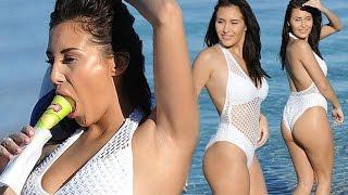 Bottoms up! Chloe Goodman in saucy fishnet swimsuit enjoys an ice pop inMexico