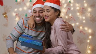 Indian husband giving surprise Christmas gift to his beautiful wife