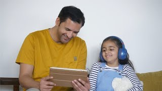 Cute little girl happily watching cartoons on a digital tablet with her father - weekend fun