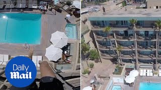 Man performs a dangerous stunt as he jumps into pool from roof - Daily Mail