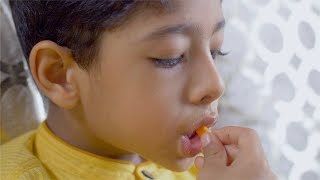 Closeup shot of an innocent Indian boy eating french fries