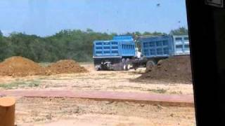 Dump trucks dumping dirt
